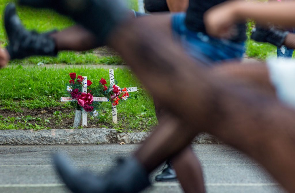 Dancers pass a memorial along WEst Broadway during the nonviolence themed Love, Peace, and Heritage parade Saturday, May 21, 2016.